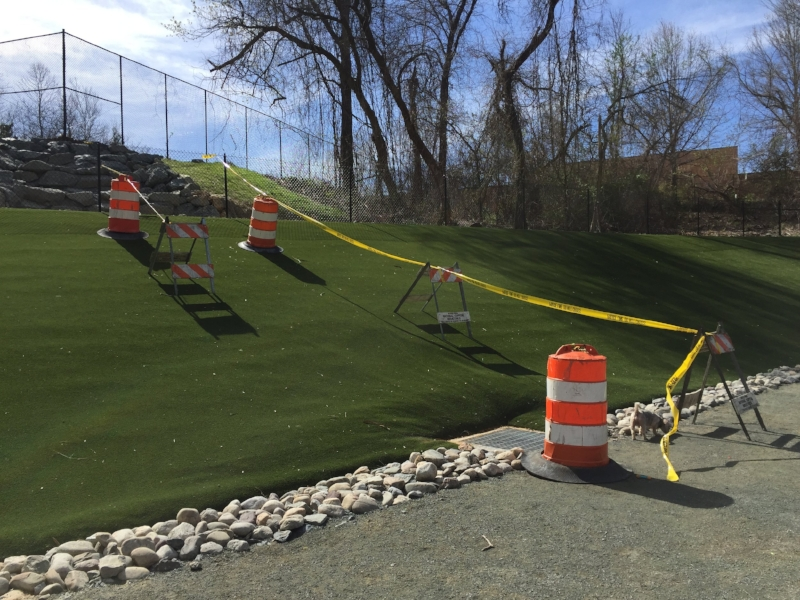 "Caution tape and barricades around area of stormwater damage. One can see ""voids"" under turf created by water moving the subsurface material."