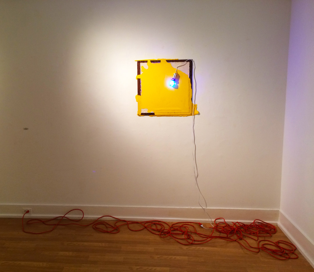 Untitled (Construction of yellow painting and blue light)   house paint, raw pigment, canvas, wood, nails, staples, blue CFL bulb, and extension cord 2013 pictured at Cora Stafford Gallery, Denton TX