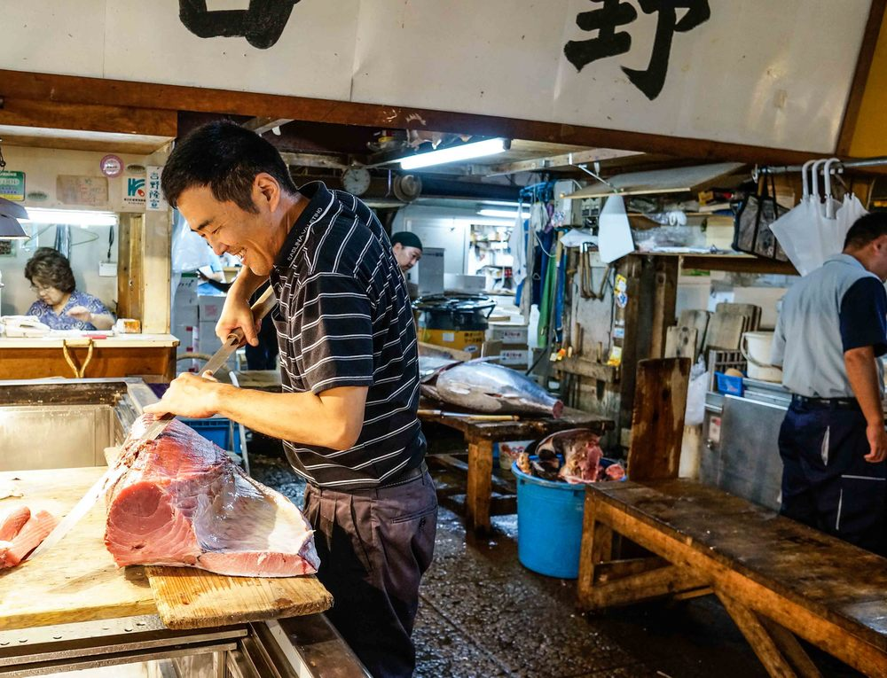 Sword wielding fish monger carving tuna at the tsukiji market