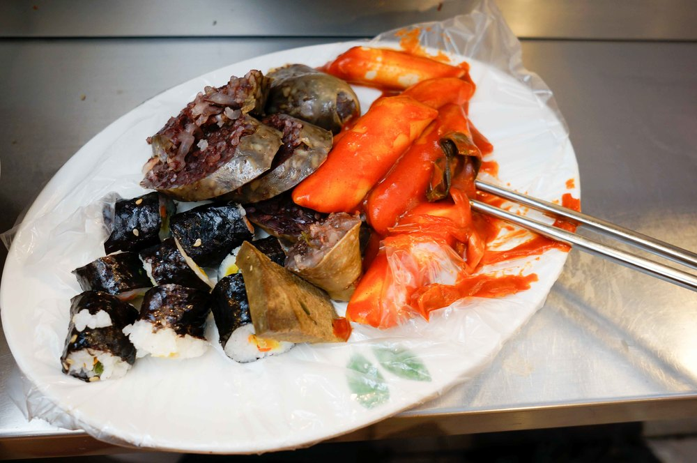 A typical street market spread: blood sausage, spicy rice cakes, seaweed rice rolls.