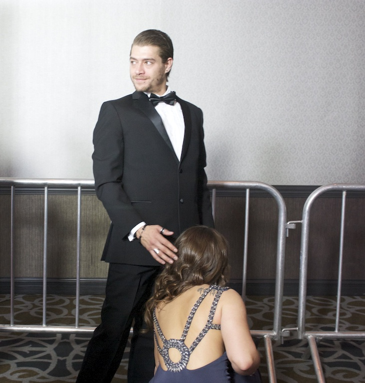 Porn star Xander Corvus waits as porn star Dani Daniels ties his shoe on the red carpet at the 2014 AVN Awards Show, Las Vegas, NV / Photo credit:  Susannah Breslin