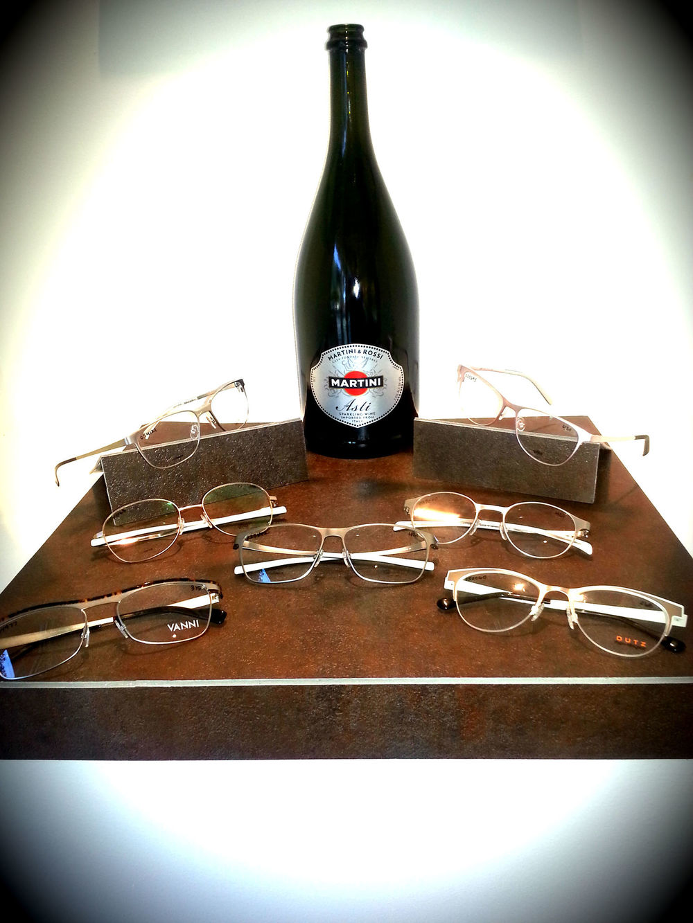 I wanted to showcase some of our shiny metal eyewear but was having a hard time figuring out how to make them pop. I found some old linoleum tiles and cut them up to create a display set. I also found a huge bottle of Asti in our recycle bin left from last nights Art Walk party that we hosted. The silver label on the Asti perfectly complimented the silver and gold tones found on the eyewear. Garbage never made my eyewear look so classy!