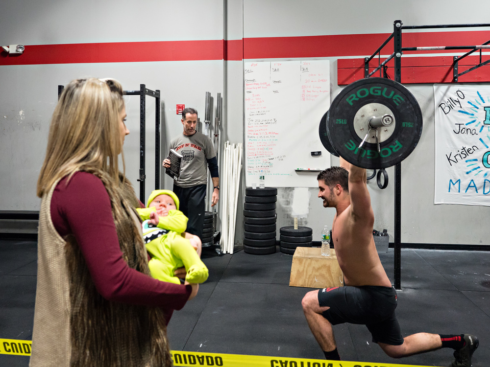 Competitor is going through 16.01 while his spouse with her baby is watching at Crossfit Persist in Matawan, NJ.