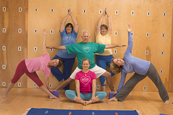 Catharine Eberhart, seated in the middle, surrounded by Purna Yoga East instructors and students with the Great Yoga Wall in the background.