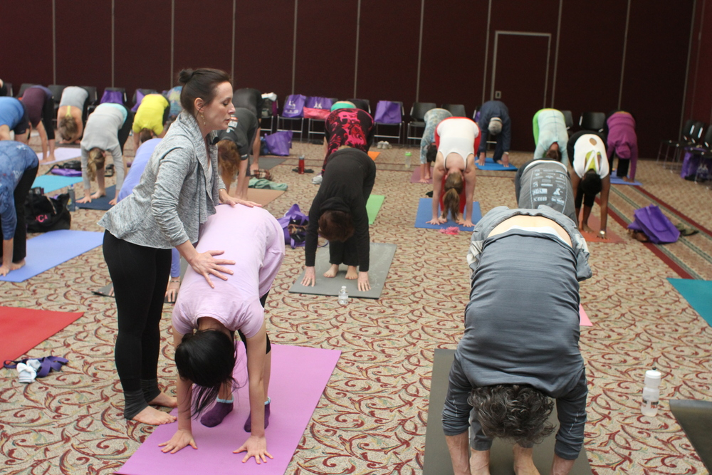 Nicole Nichols, owner of Republic of Yoga, giving a participant an adjustment