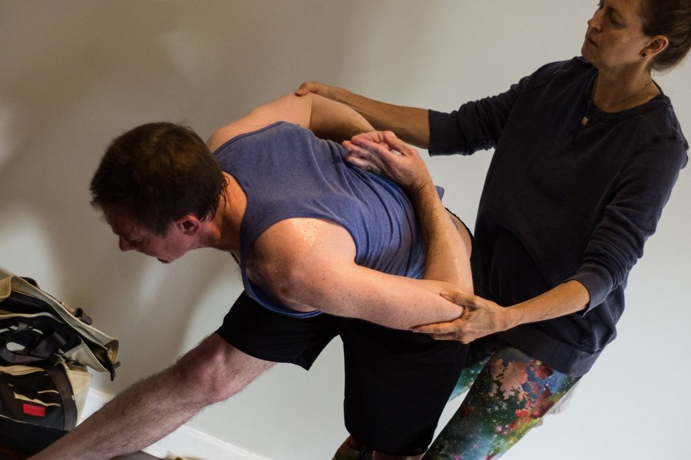 Stacy adjusting a student in an ashtanga class