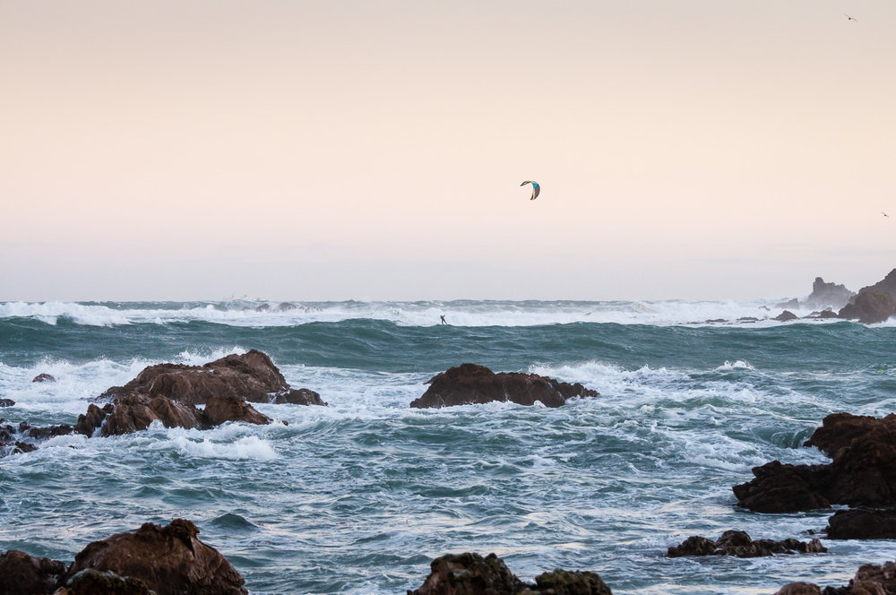 A kite surfer dwarfed by rough seas, headed for the rocks by the island Taputeranga, at Island Bay.