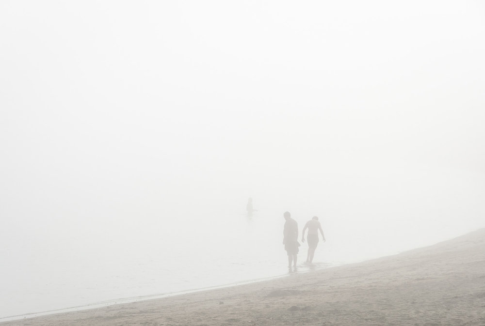 Together but in their own worlds, three people at the beach, enveloped by dense mist