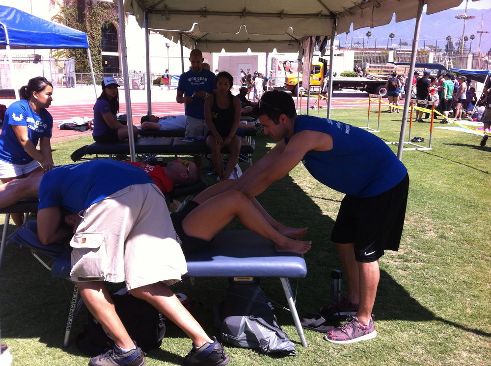 Dr. Santos and Victor Bonilla working on a CrossFit athlete.