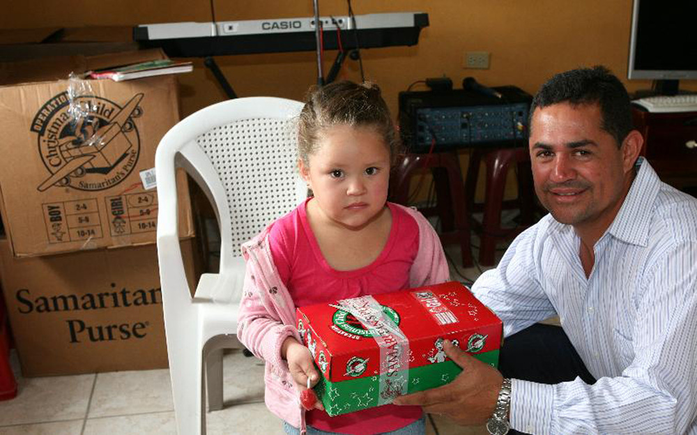 web.pastor and girl with Samaritans purse box.jpg