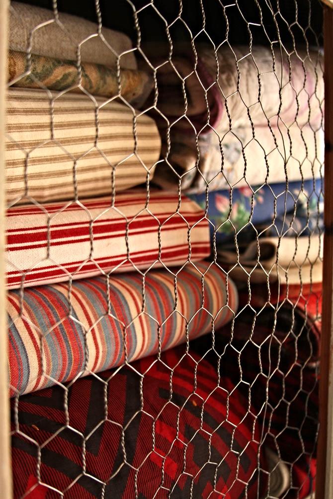Hiden Galleries: vintage quilts in white cabinet w/chicken wire fronts