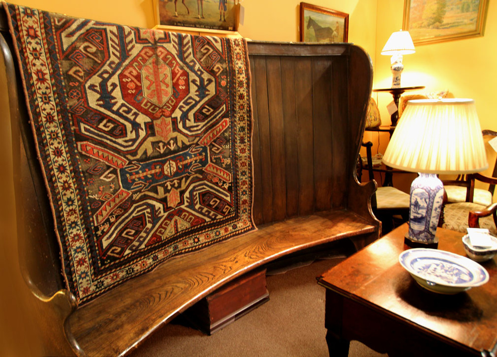 Kazak carpet on rare 18th-century elmwood settle, English