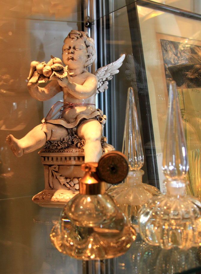 Hiden Galleries: Italian porcelain cherub with vintage perfume bottles