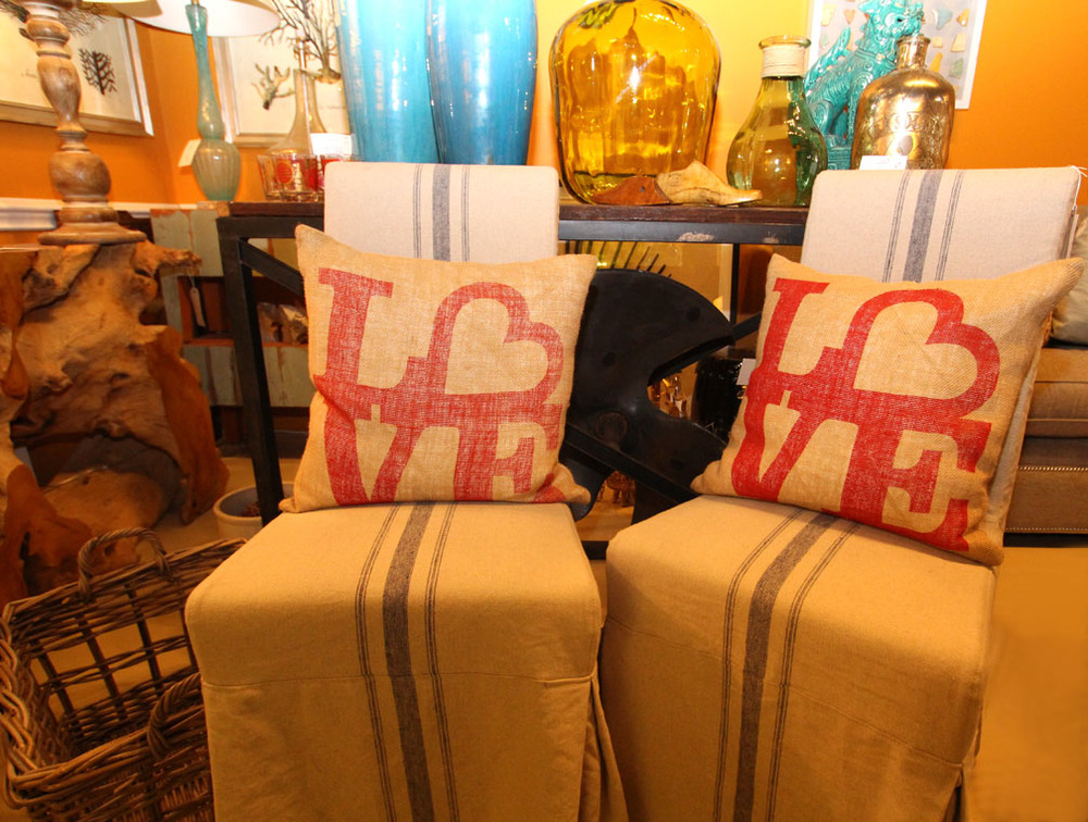 "Hiden Galleries: ""Love"" pillows on corseted dining chairs in front of a propeller console table"