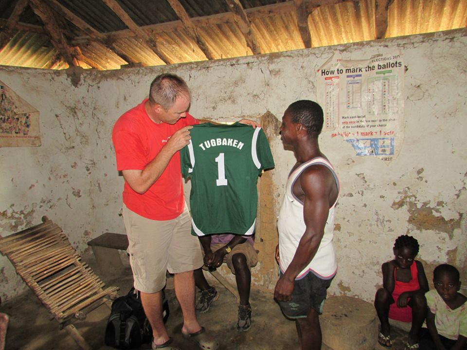 Adam Demark giving out the new soccer jerseys to the village team