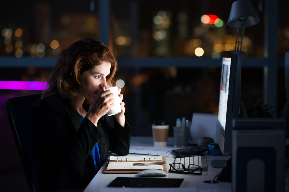 Woman drinking coffee at her computer