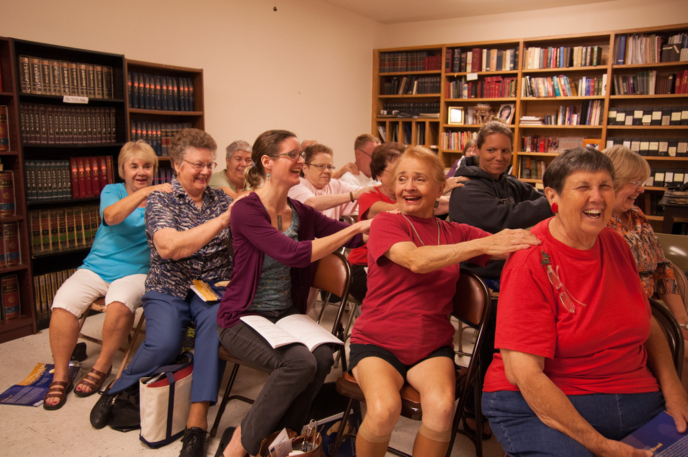 The St. Mark United Methodist Church choir warms up before the start of their practice by massaging each other's shoulders Thursday, Oct. 10. The choir spent the following hour practicing their inflection and pitch of church hymns. Cardona's wife, Shawna Cardona (pictured second row, second from the right), also attends weekly choir practices.