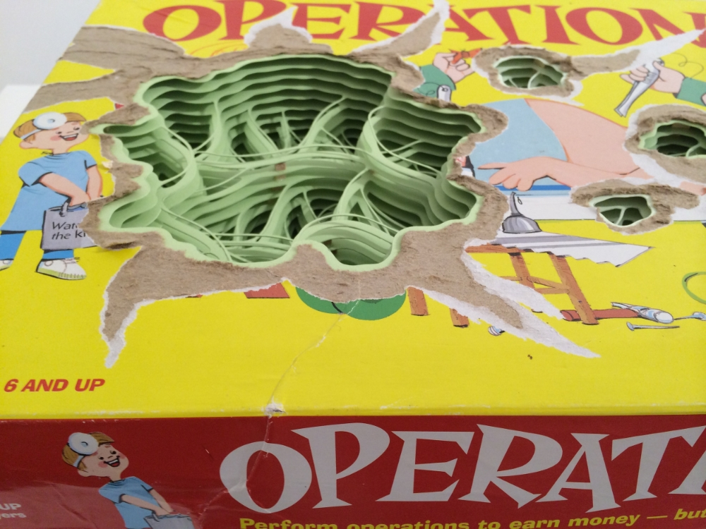 Operation (detail),  2014, hand-cut paper sculpture, found board game and wood, 10.5 x 15.75 x 3.25 inches, $1000.