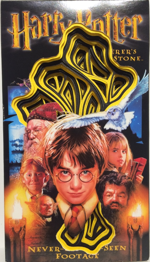 Harry Potter (Yellow) , 2015 hand-cut paper and VHS cover,   7.5 x 4.25 x 1, $200.