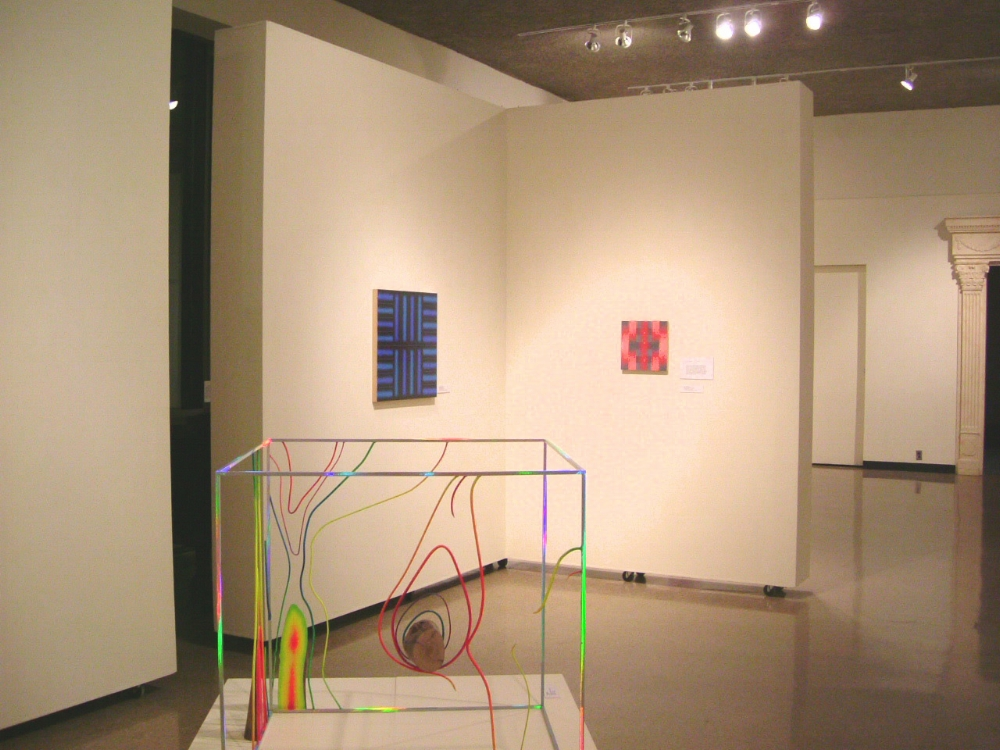 David Shaw,  Knot , 2004, holographic laminate and paint on steel and wood, 35.75 x 46.5 x 37.75 inches (sculpture on pedestal)   Katia Santibañez,  Blue Partition , 2004, acrylic medium on wood, 24 x 24 inches (left wall)  Katia Santibañez,  Dialogue on a Red Bed , 2005, acrylic medium on wood, 12 x 12 inches (right wall)