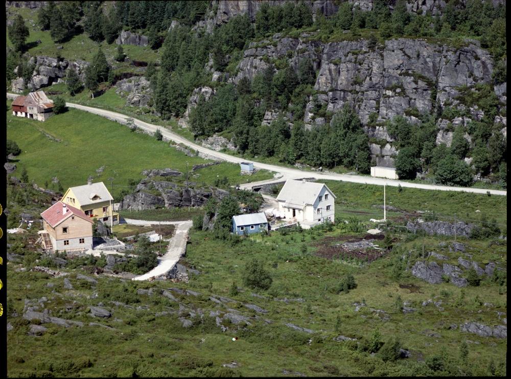 Litt mer om dette bildet som AV presenterte: Det var i kjelleren i huset i midten (tilhørende Bergfjord) at Sigmund Juvik startet opp en dagligvarehandel i 1952. I 1972 bygde han et nytt forretningsbygg i området til høyre i bildet. Dette bygget har huset div. butikker opp gjennom årene, og er blitt utvidet flere ganger. I dag huser det Janco Expert og BOA sykler. Den store fjellknausen mellom husene ble sprengt vekk da det ble bygget en bensinstasjon der Bergfjords hus står, samtidig som veien ble lagt om. I disse dager fjernes også bensinstasjonen slik at det kan bygges et nytt forretningsbygg på denne tomten.
