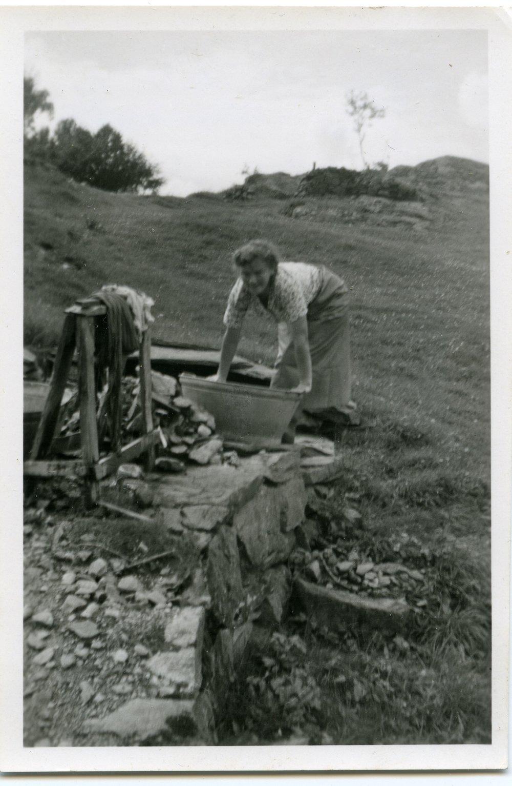 Bildet viser Amanda Haugland og klesvask på gamlemåten. Foto: Jon Haugland