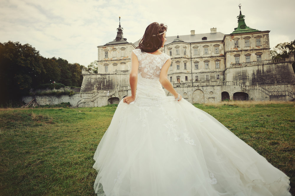 gorgeous  bride walking next to castle