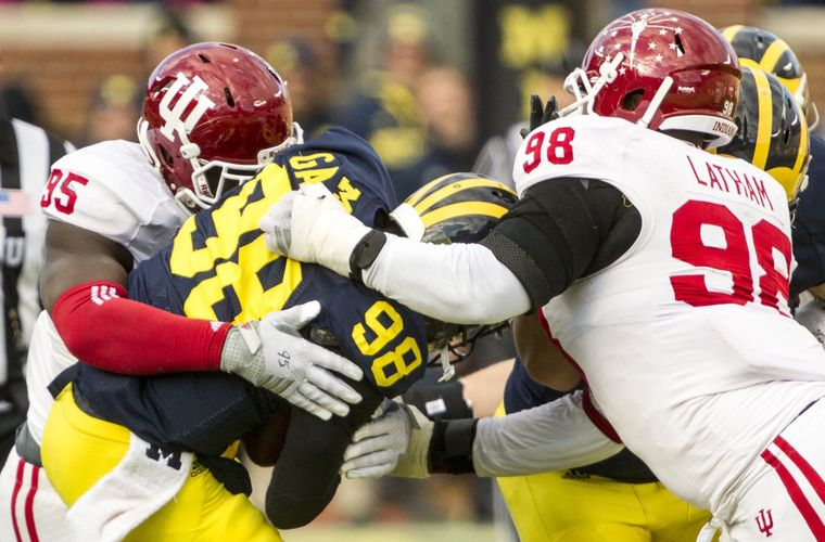Bobby Richardson (95) and Darius Lathum (98) converge for the sack on Michigan Quarterback Devin Gardner. Photo Credit - Herald Times