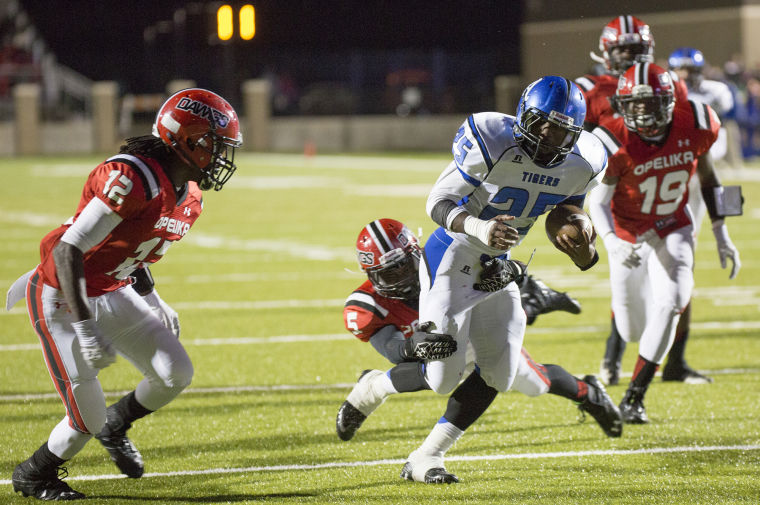 Tyus Flakes carries the ball against Opelika, dragging defenders towards the goal line. Photo Credit - Albert Cesare oanow.com