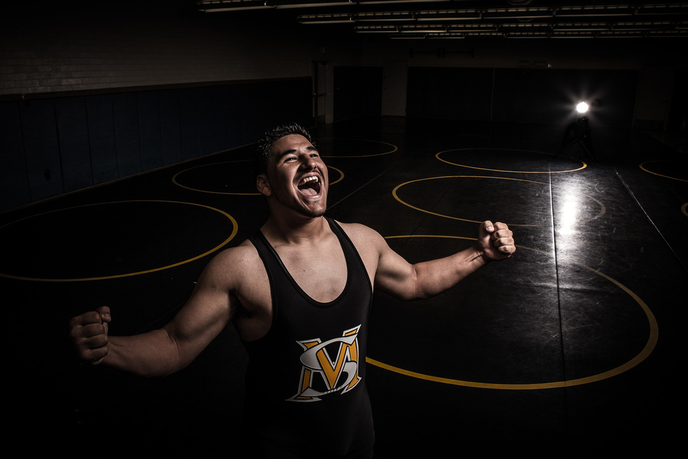 Damian is a muscular state champion wrestler and we got really creative with his session. The wrestling room was the perfect studio for this shot. I placed a strobe far behind him to create a light burst effect and also to give him a bit of rim light. I then placed another strobe with a soft box to his left to light his face and body. The flexing and expression really gave this image life!