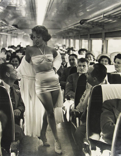 Dan Weiner,  A fashion show on board the New York , New Haven, and Hartford Railroad's Show Train, 1949. Gelatin silver print.  At the booth of Howard Greenberg Gallery