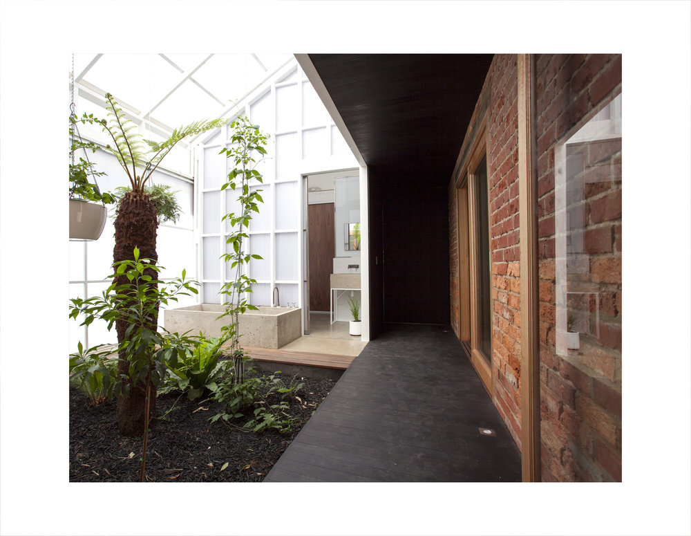 The lush internal green courtyard with an in situ bath for guests inside the house open to the hallway is all about getting light and warmth into the house through the thinner transparent skin during the day, but is zoned off during the night as the house contracts for warmth.