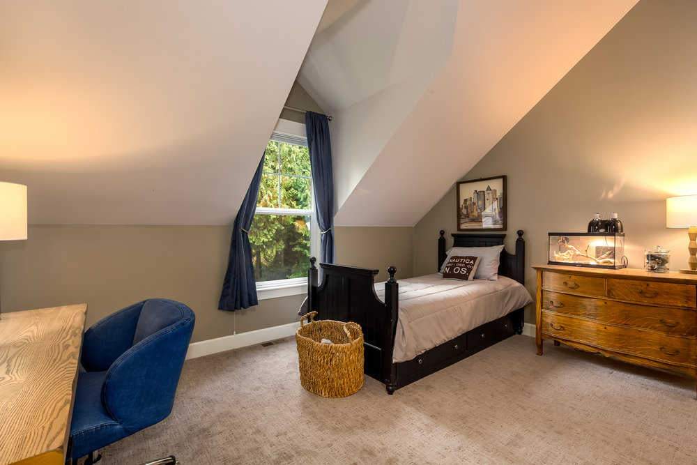 This bedroom upstairs is quaint and warm with a window snuggled into the vaulted ceiling. Plus, a light above the closet (not pictured) serves as mood lighting or a nightlight.