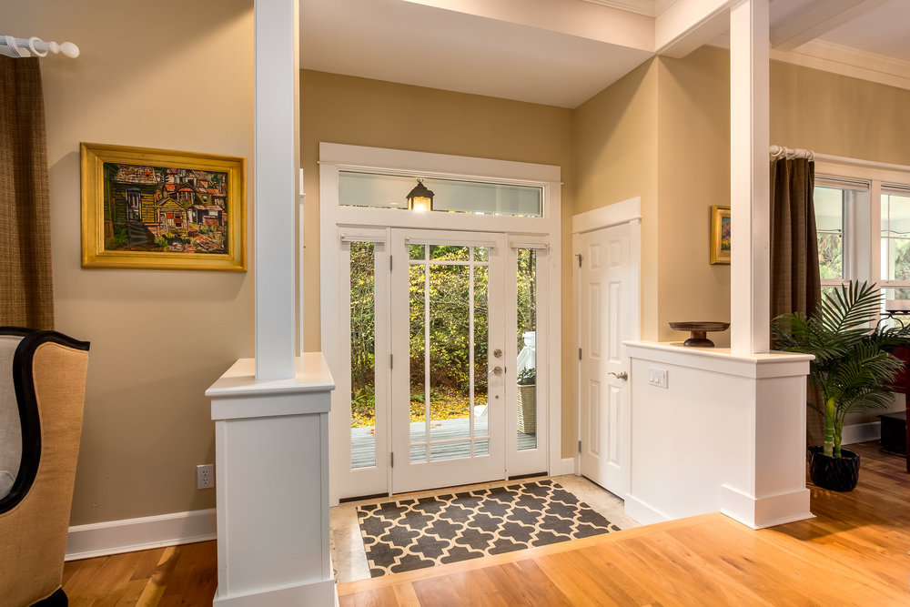 A glass front door with transom windows surrounding brings natural light to the entrance. Either side of the front door has a coat closet and flanking the steps up to the interior are solid, bold columns adding to the grand entrance. Welcome home!