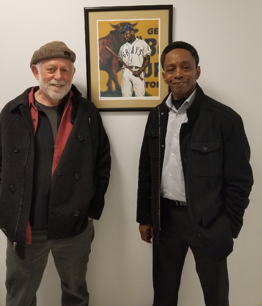 Youth Academy hallway is lined with photos & paintings of African American baseball heroes of the past. Here filmmaker Eugene Corr and Coach Roscoe Bryant are in front of the great Josh Gibson.