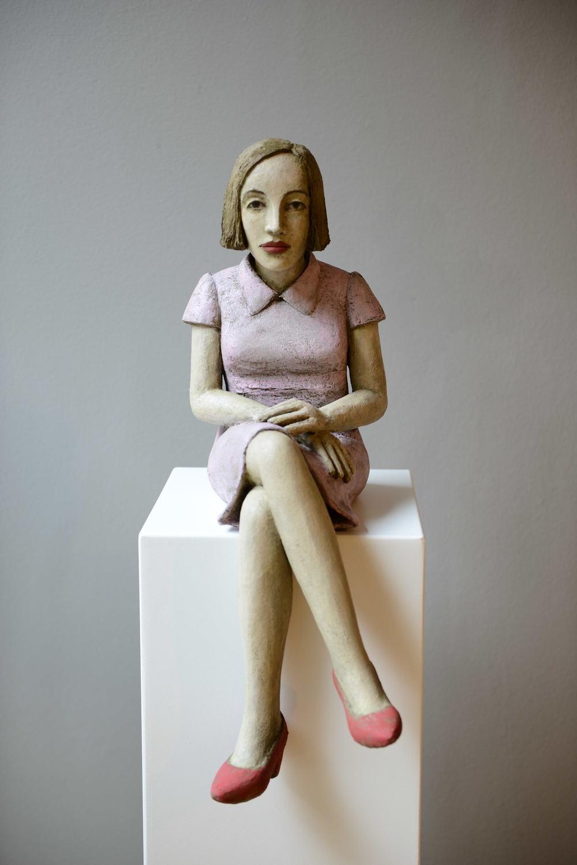 Sitzende Frau mit rosafarbenem Kleid