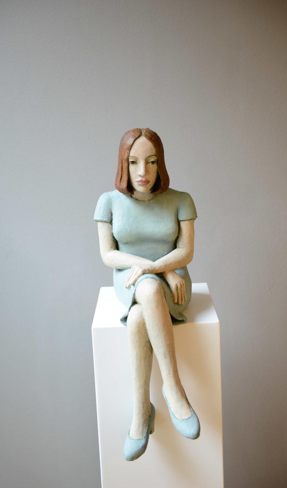 Grosse sitzende Frau mit blauem Kleid