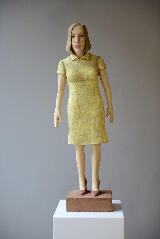 Stehende Frau mit gelbem Kleid