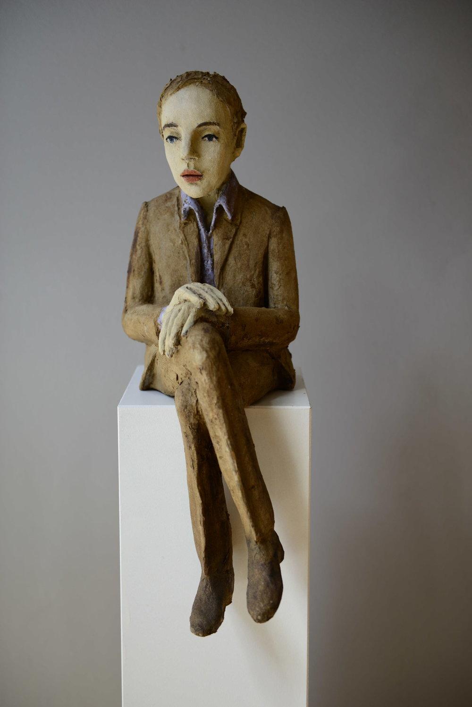 Sitzender Mann mit hellbraunem Anzug