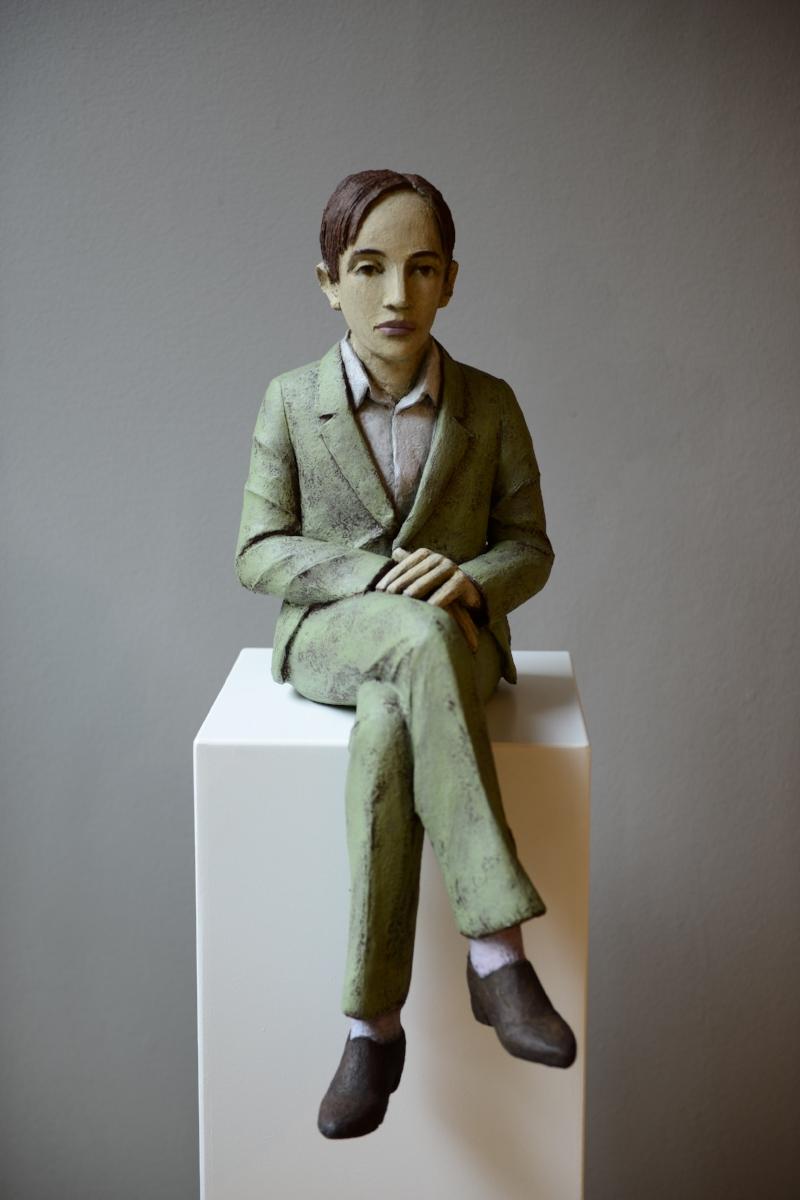 Sitzender Mann mit hellgrünem Anzug