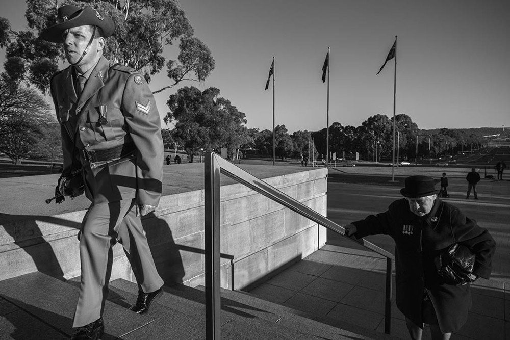 A bugle player from the ADF enters the War Memorial along side a woman whose father served in World War One.