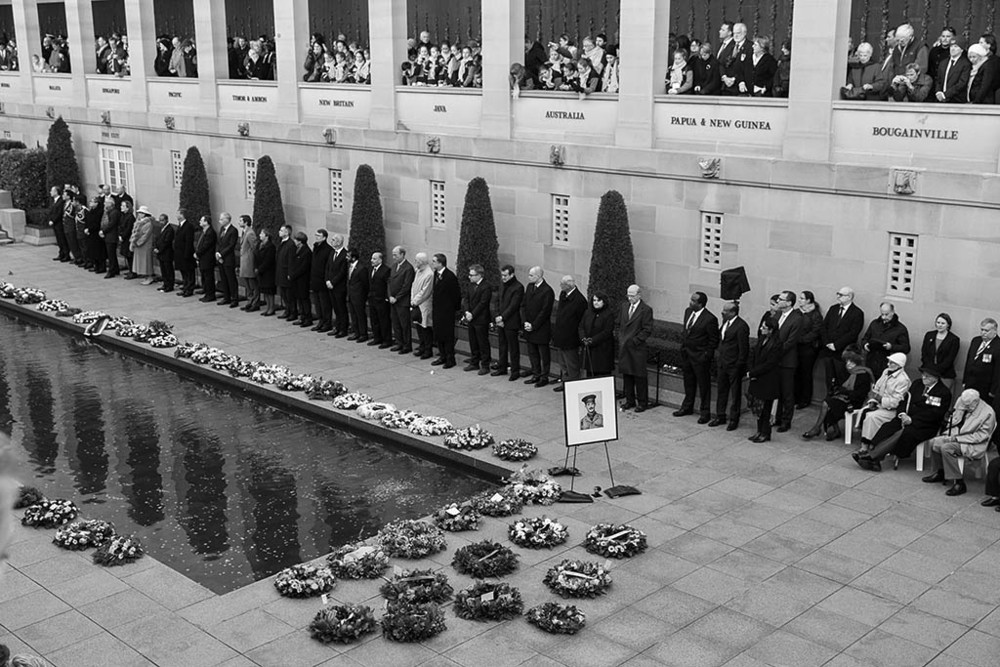 Members of diplomatic community pay their respects by the Pool of Remembrance with a framed photo of Keith Heritage on display.
