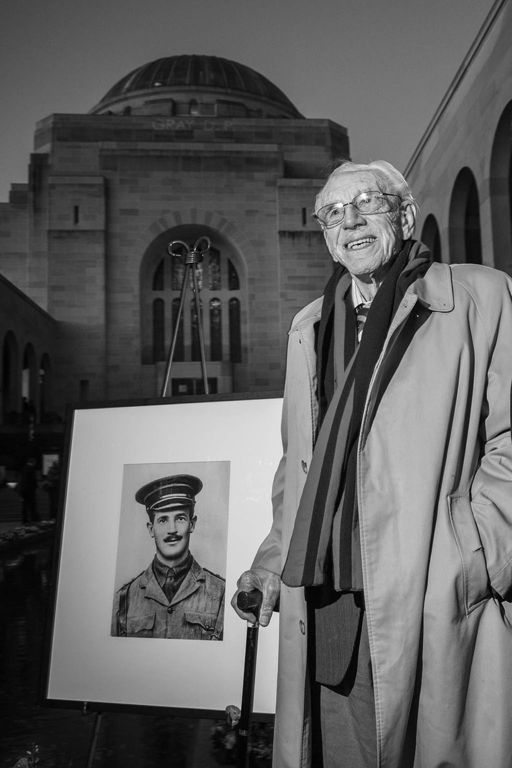 WW2 veteran Ron Metcalfe stands beside a portrait of WW1 soldier Keith Heritage.
