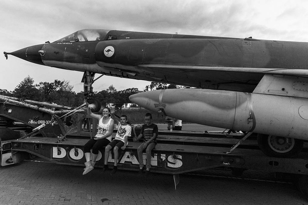 Tyla, Rhys and Brody Gilkes from Hilltop on the back of the transport truck with the fighter jet, waving to passing trucks at Pheasants Nest.