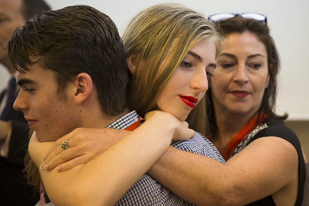 Georgie Stone embraces her twin brother Harry with mum Rebekah Robertson after addressing the forum.