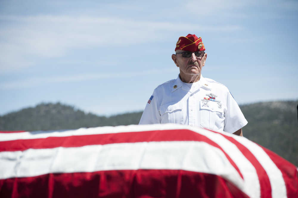Chuck Teague of the U.S. Marine Corps stands  behind the symbolic casket during the Memorial Day ceremony at Veterans Park May 29, 2017.