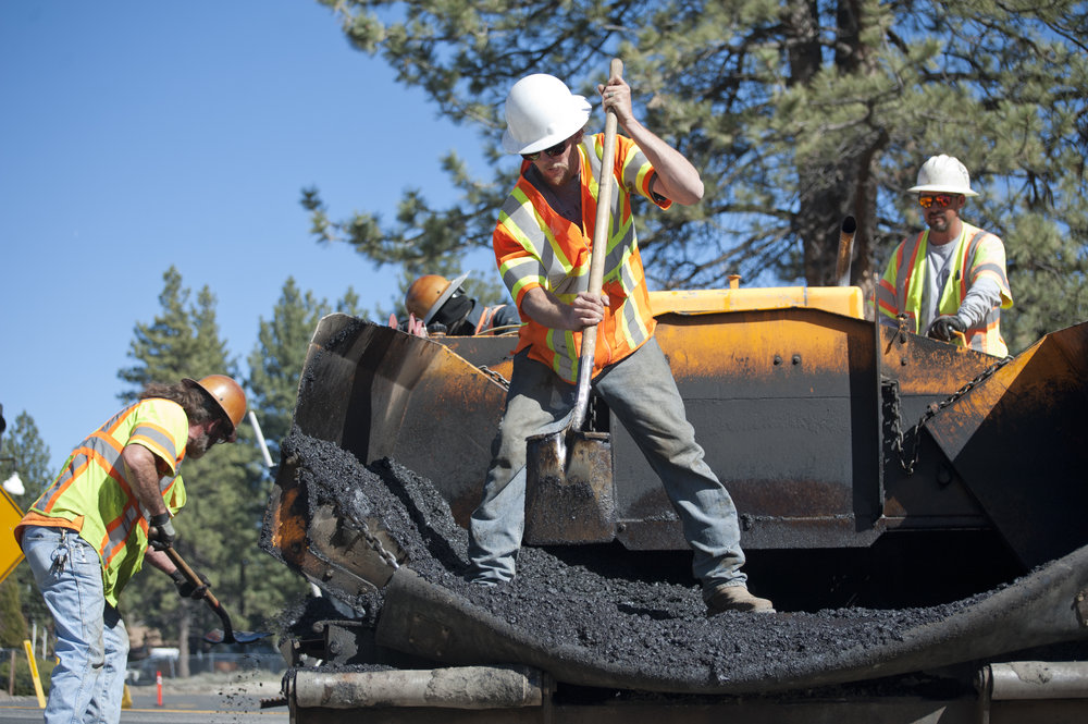 Matt Hayes, center, consolidates the asphalt mix while Bear Valley Paving crews work to expand Big Bear Boulevard April 20, 2017.