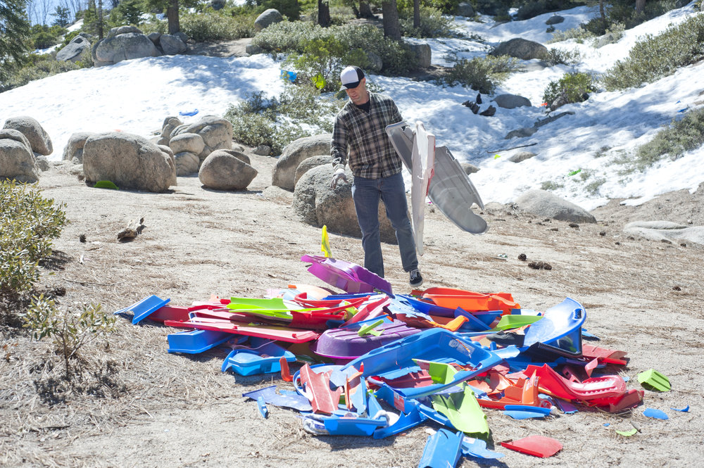 Jonathan Duarte tosses plastic sled scraps into a pile during The Mountain Clean Up Project April 1, 2017.