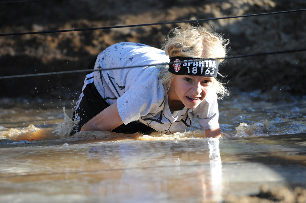 Jonathan Hoak crawls through a water obstacle during the Spartan Kids Race at Snow Summit Oct. 27, 2017.
