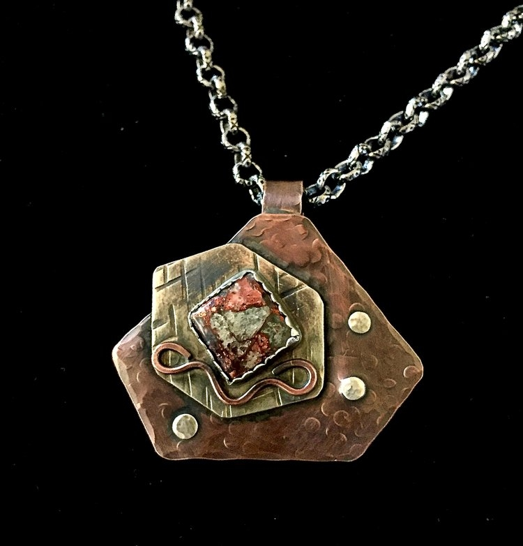 "- The geometric designs in copper and sterling silver of the ""Collett"" pendant features a quartz/copper inlay stone and sterling silver rivets."